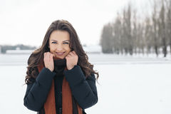 Portrait of smiling young woman in winter park. Royalty Free Stock Image