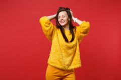 Portrait of smiling young woman in yellow fur sweater keeping eyes closed, clinging to head isolated on bright red. Background in studio. People sincere royalty free stock images