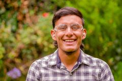 Portrait of smiling young worker wearing transparent safety glasses, long sleeve shirt and ear plugs, in a blurred. Nature background Stock Photography