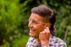 Portrait of smiling young worker wearing transparent safety glasses, and wearing a long sleeve shirt, putting ear plugs. To protect from noise, in a blurred Royalty Free Stock Image