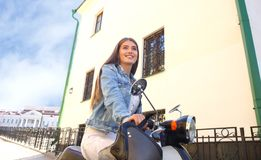 Portrait smilling beautiful girl sitting on retro scooter. Stock Photos