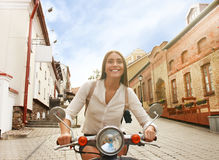 Portrait smilling beautiful girl sitting on retro scooter. Stock Image
