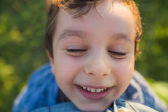 Portrait of smilling cute little boy wiht closed eyes (tilt view) Stock Photos