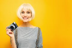 Portrait of a smilling girl with a camera in hand on a yellow background. Isolated studio. blonde wig