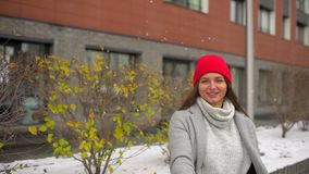 Portrait of smilling young beautiful woman, hister happy girl 20s with long hair in stylish autumn walking, having fun. Throwing snowball on autumn, winter stock footage