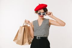 Portrait of a smilng woman wearing red beret. And sunglasses holding shopping bags isolated over white background Royalty Free Stock Images