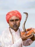 Portrait snake charmer adult man in turban and cobra sitting near the lake. Pokhara, Nepal Royalty Free Stock Photography
