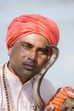 Portrait snake charmer adult man in turban and cobra sitting near the lake. Pokhara, Nepal Stock Photography