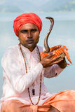 Portrait snake charmer adult man in turban and cobra sitting near the lake. Pokhara, Nepal Royalty Free Stock Images