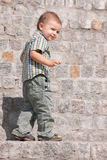 Portrait of a sneaky boy. A sneaky toddler is creeping on the stone stairs Royalty Free Stock Photos