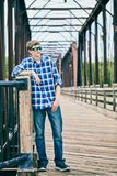 Portrait of snobbish young man standing on bridge. Portrait of snobbish young Caucasian man wearing checked shirt and sunglasses standing on bridge and looking royalty free stock images