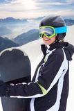 Portrait of snowboarder  on background beautiful landscape of snowy high mountains. WinterSport, Snowboarding - portrait of young snowboarder girl at the ski Royalty Free Stock Images