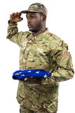 Portrait of soldier holding an american flag and saluting Stock Images