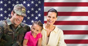 Portrait of soldier reunited with family. Against american flag in background stock image