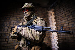Portrait of soldier with a weapon. A man in military uniform with a gun standing at attention stock photo