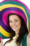 Portrait and the sombrero. Nice portrait of a brunette with a grat smile wearing a big colored hat like a sombrero Stock Image