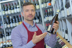 Portrait sommelier with wine bottle in wine shop Royalty Free Stock Photos