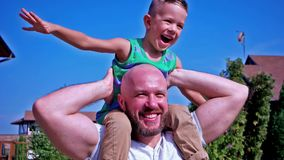 Portrait of the son and the father, child sitting on the shoulders of his dad happy family having fun laughing