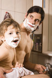 Portrait of son and father enjoying while shaving together Royalty Free Stock Photos