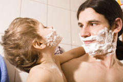 Portrait of son and father enjoying while shaving together Royalty Free Stock Image