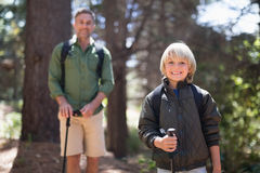 Portrait of son and father hiking on sunny day. In forest stock photos