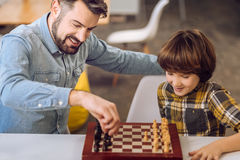 Portrait of son and father while playing chess. My turn. Handsome men wearing jeans shirt holding pawn in his hand while thinking of right move stock photos