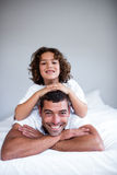 Portrait of a son lying on fathers back Stock Images