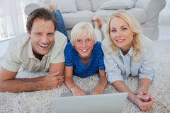 Portrait of son and parents using a laptop. Lying on a carpet Royalty Free Stock Images