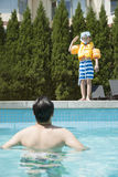 Portrait of son with snorkeling equipment standing by the pool as father waits in the water Stock Image
