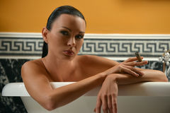 Portrait of sophisticated brunette woman. In the bath holding cigar Stock Images