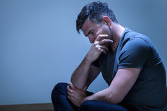 Portrait of sorrowful, grieving man. Sitting on the floor Stock Photo