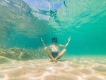 Portrait sous-marin de l'homme en position de yoga sous l'eau en mer image libre de droits
