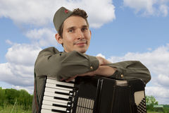 Portrait of Soviet soldier with accordion. Portrait of Soviet soldier in uniform of World War II with accordion on the blue sky background stock image