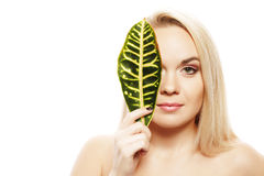 Portrait of a spa woman with leaf of tropic plant. Portrait of a spa woman. Beautiful blonde girl after bath hides a half of her face with a leaf of plant Royalty Free Stock Photography