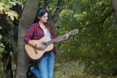 Portrait of Spanish guitar player student girl leaning tree trunk at fall forest background Stock Image