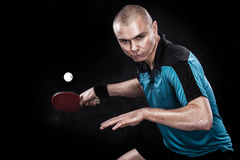 Portrait of sports man, male, athlete playing table tennis isolated on black background. Young sports man table tennis player is playing isolated on black Stock Photo
