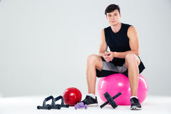 Portrait of a sports man sitting on the fitness ball Royalty Free Stock Images