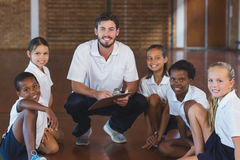 Portrait of sports teacher and school kids. In basketball court at school gym Stock Photo