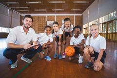 Portrait of sports teacher and school kids in basketball court Royalty Free Stock Photo