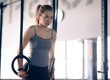 Portrait of Sports Woman Training with Gymnastic Rings in the Gym. Fitness and Healthy Lifestyle Concept. royalty free stock photo