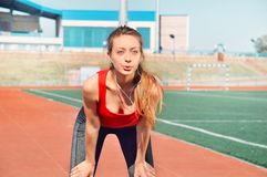 Portrait of a sports woman warming up at outdoor stadium Royalty Free Stock Image