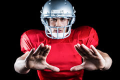 Portrait of sportsman defending while playing American football Stock Images