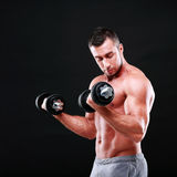 Portrait of a sportsman lifting dumbbells Stock Photos