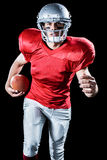 Portrait of sportsman running while playing American football Stock Images