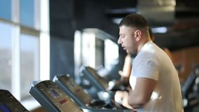 The portrait of sportsman who runs on the treadmill in luxury gym. The man wears white t-shirt and electronic wrist whatches during his training. The race stock video