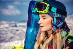 Sportswoman with snowboard. Portrait of a sportswoman wearing helmet and mask with snowboard in hand looking a side, enjoying sunny frosty day, perfect day for royalty free stock image