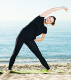 Portrait of sportswoman which is practicing stretching in black. T-shirt on the beach near sea Royalty Free Stock Photos