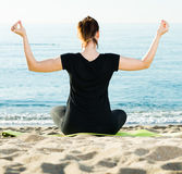Portrait of sportswoman which is sitting her back and practicing. Asana in black T-shirt on the beach Royalty Free Stock Images