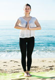 Portrait of sportswoman which is staying and practicing asana in. White T-shirt on the beach Stock Image
