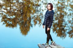 Portrait of sporty beautiful adult brunette woman the fall city park posing near blue lake with autumn trees reflections. Warm cloudy weather. Outdoors Stock Photo